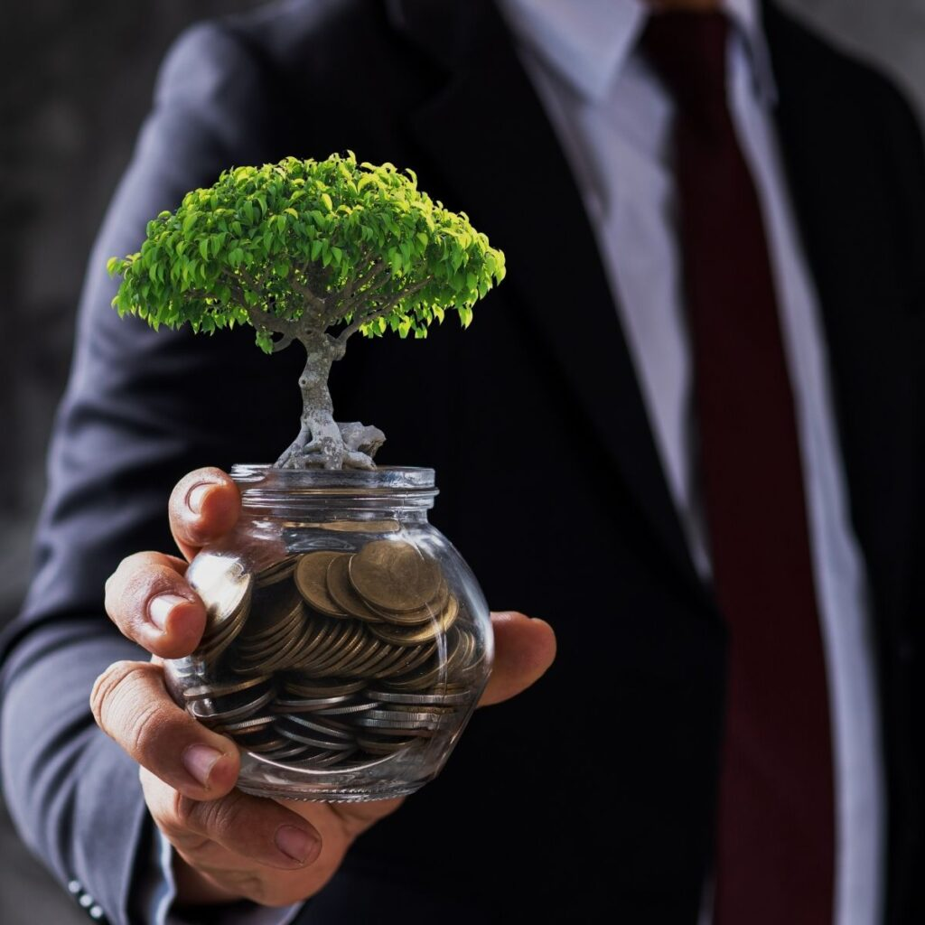 a man in a suit holding a jar with coins and a small tree growing out of it