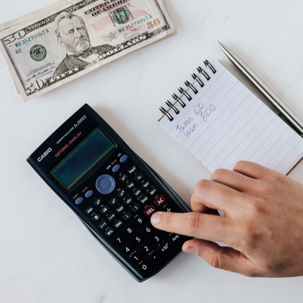hands using a calculator with a notepad and $50 on the side