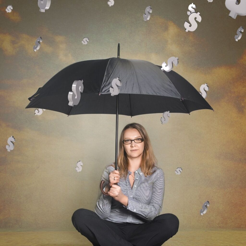 a woman holding an umbrella with dollar signs falling down