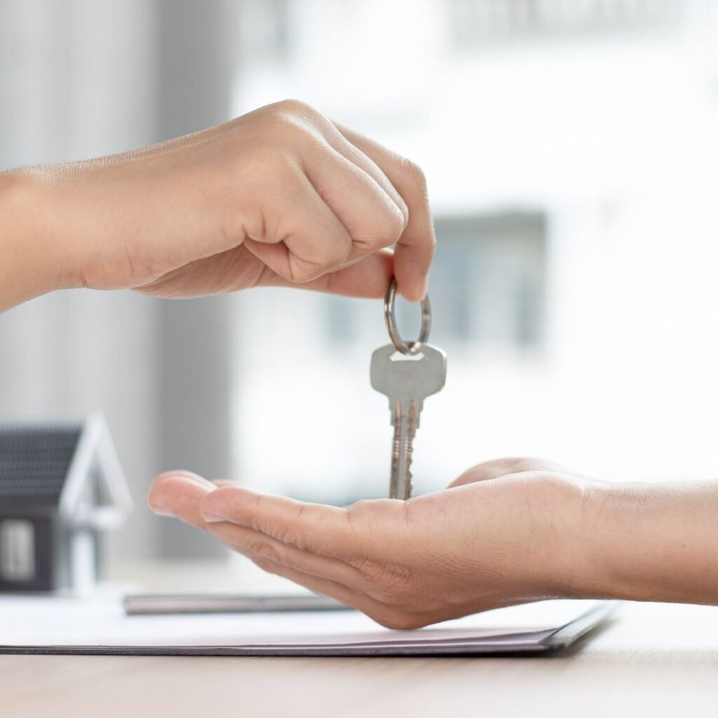 a hand handing a key over to another hand