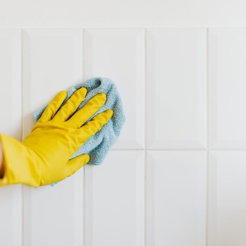 a hand with a yellow glove on wiping off tile