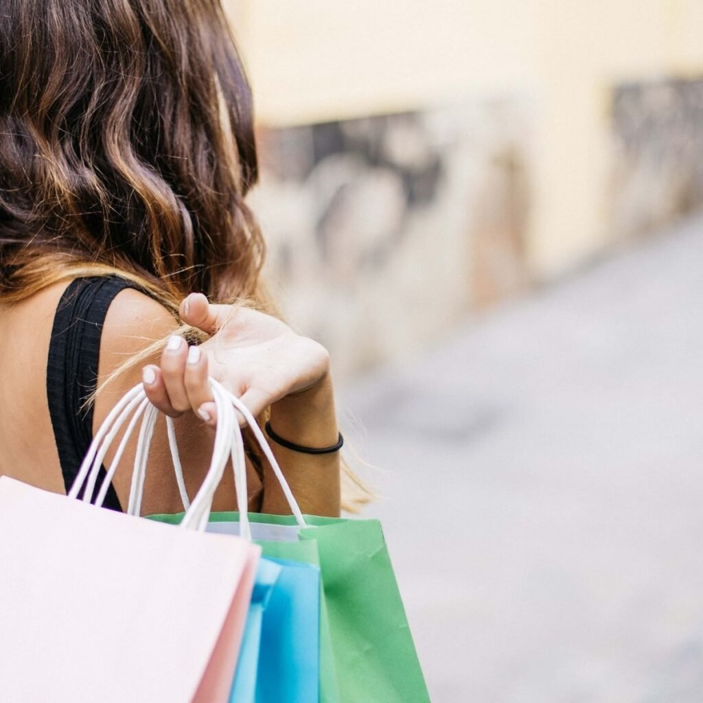 woman holding shopping bags over her shoulder