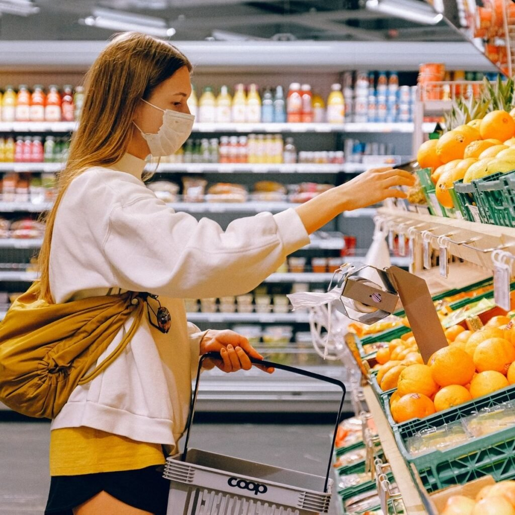 a woman picking out produce in a grocery store