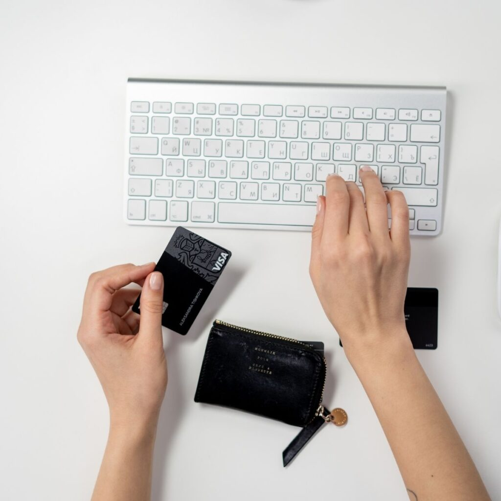 hands holding a credit card typing on a laptop